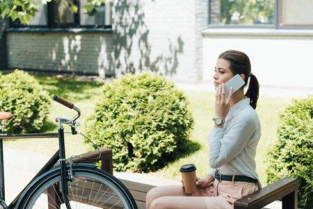 Photo pour Belle femme d'affaires parlant sur smartphone et tenant tasse en papier près de vélo - image libre de droit