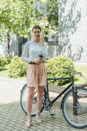Photo pour Attrayant femme d'affaires parlant sur smartphone et tenant tasse en papier tout en se tenant près du vélo - image libre de droit