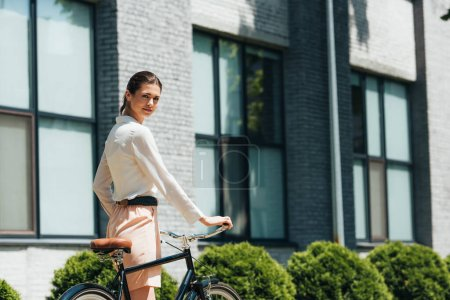attractive businesswoman walking with bicycle near modern building