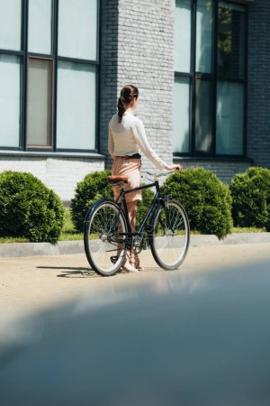 selective focus of businesswoman walking with bicycle near modern building