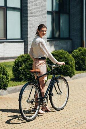 Photo pour Femme d'affaires joyeuse marche avec vélo près du bâtiment moderne - image libre de droit