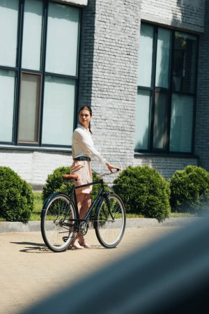 selective focus of attractive businesswoman walking with bicycle near modern building