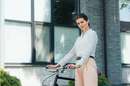 beautiful young businesswoman standing with bike near modern building