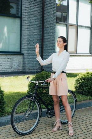 Photo pour Heureuse jeune femme d'affaires debout avec vélo et agitant la main - image libre de droit