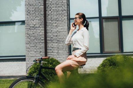 Photo pour Foyer sélectif de la femme d'affaires dans les lunettes parler sur smartphone et assis sur vélo - image libre de droit