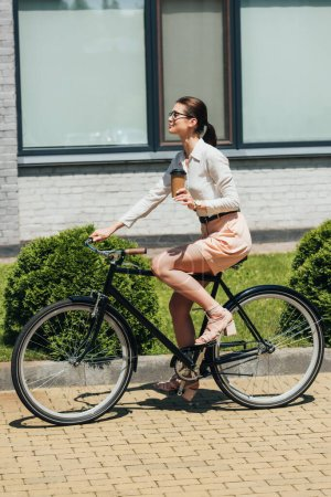 Photo for Attractive businesswoman in glasses riding bicycle and holding paper cup - Royalty Free Image