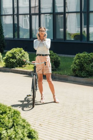 attractive businesswoman in glasses listening music and touching wireless headphones while standing near bicycle