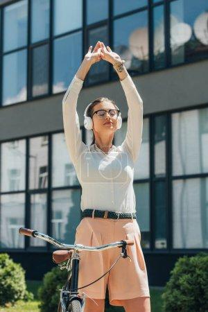 Photo pour Belle femme d'affaires dans des lunettes écouter de la musique et debout avec les mains au-dessus de la tête près du vélo - image libre de droit