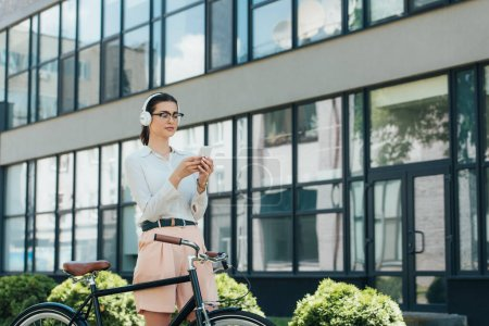 Photo for Attractive businesswoman in glasses listening music in wireless headphones and using smartphone near bicycle - Royalty Free Image