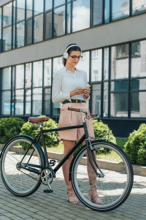 Photo for Beautiful businesswoman in glasses listening music in wireless headphones and using smartphone near bicycle - Royalty Free Image