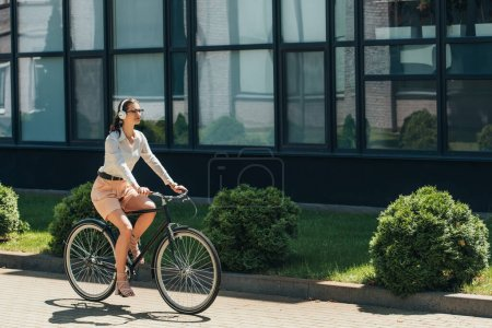 beautiful businesswoman in glasses listening music in wireless headphones and riding bicycle near building
