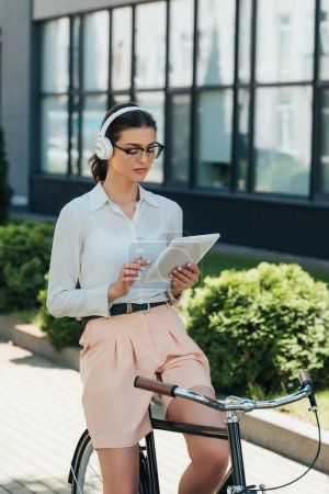 Photo for Businesswoman in glasses listening music in wireless headphones and using digital tablet near bike - Royalty Free Image