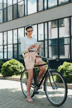Photo for Attractive businesswoman in glasses listening music in wireless headphones and using digital tablet while sitting on bike - Royalty Free Image