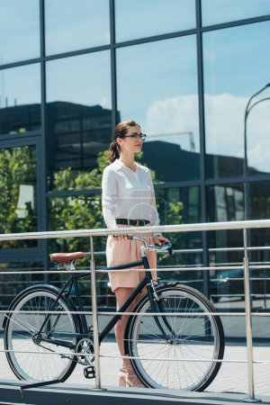 attractive businesswoman in glasses standing near modern bike and building