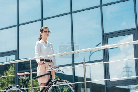 bonita mujer de negocios en gafas de pie con bicicleta cerca del edificio