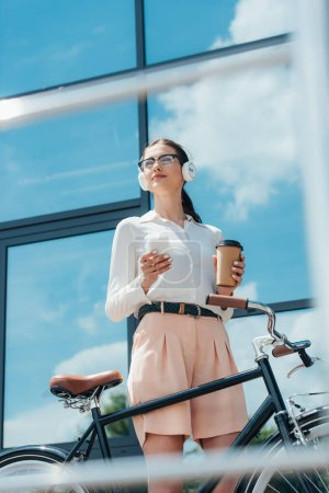 selective focus of businesswoman in wireless headphones holding smartphone and paper cup near building