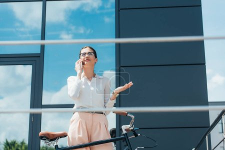 selective focus of cheerful businesswoman in glasses talking on smartphone near building and bicycle