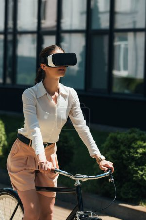 Photo for Businesswoman in virtual reality headset riding bicycle near building - Royalty Free Image