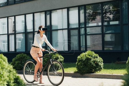 Photo for Selective focus of young businesswoman in virtual reality headset riding bicycle near building - Royalty Free Image