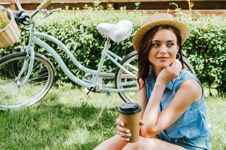 Photo pour Fille en chapeau de paille tenant tasse en papier et assis près du vélo - image libre de droit