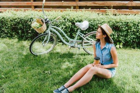 Photo pour Femme en chapeau de paille tenant tasse en papier et assis sur l'herbe près du vélo - image libre de droit
