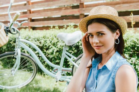 attractive woman touching straw hat and smiling near bicycle