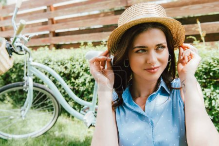 Photo for Attractive woman touching straw hat near bicycle and fence - Royalty Free Image