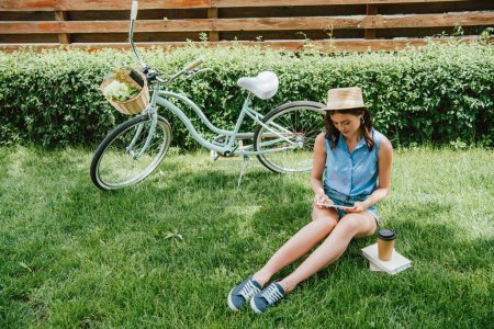 Photo for Girl in straw hat using digital tablet and sitting on grass near bicycle, paper cup and books - Royalty Free Image