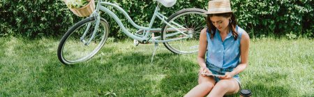 panoramic concept of girl in straw hat using digital tablet while sitting on grass near bicycle