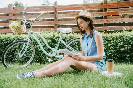 Photo for Girl in straw hat looking at digital tablet and sitting on grass near bicycle, paper cup and book - Royalty Free Image