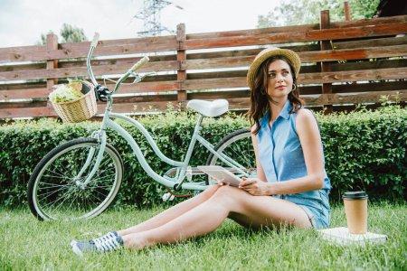 Photo pour Femme en chapeau de paille tenant tablette numérique et assis sur l'herbe près de vélo, tasse en papier et livre - image libre de droit