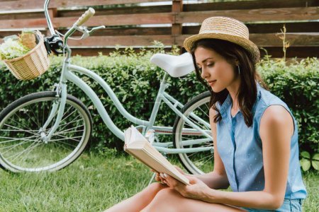 Photo for Stylish girl in straw hat reading book and sitting on grass near bicycle - Royalty Free Image
