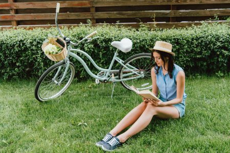 trendy girl in straw hat reading book and sitting on grass near bicycle with wicker basket