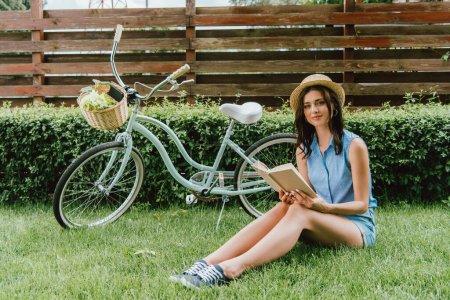 Photo pour Heureuse fille en paille chapeau tenant livre et assis sur l'herbe près de vélo - image libre de droit