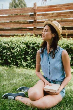 Photo pour Heureuse fille en paille chapeau tenant livre et assis sur l'herbe - image libre de droit