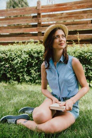 Photo pour Femme heureuse en chapeau de paille tenant le livre et assise sur l'herbe verte - image libre de droit
