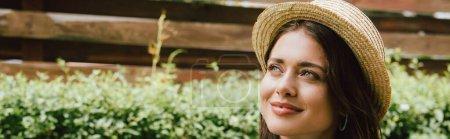 Photo pour En-tête de site Web de femme rêveuse en chapeau de paille souriant et détournant les yeux - image libre de droit