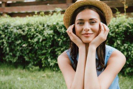 Photo pour Joyeuse jeune femme en chapeau de paille touchant le visage et regardant la caméra - image libre de droit