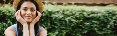 Photo pour Site web tête de jeune femme gaie en chapeau de paille toucher le visage et en regardant la caméra - image libre de droit