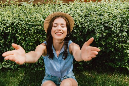 Photo for Selective focus of happy girl in straw hat with outstretched hands sitting near bush - Royalty Free Image