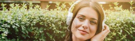 Photo pour Plan panoramique de jeune femme joyeuse écoutant de la musique dans des écouteurs sans fil près de la brousse - image libre de droit