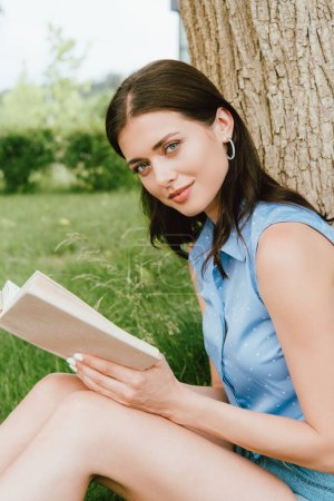 Photo for Beautiful young woman looking at camera wile holding book outside - Royalty Free Image