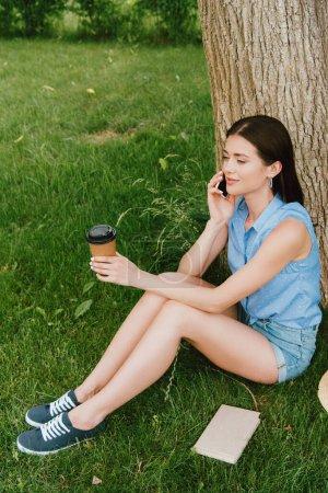 belle femme parlant sur smartphone et tenant tasse en papier tout en étant assis sur l'herbe