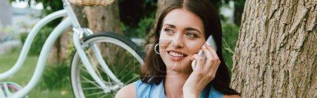 Panoramaaufnahme einer glücklichen Frau, die in der Nähe eines Fahrrads mit dem Smartphone spricht