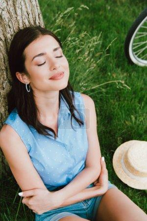 Photo pour Vue grand angle de belle femme souriant tout en étant assis près du tronc d'arbre et chapeau de paille - image libre de droit