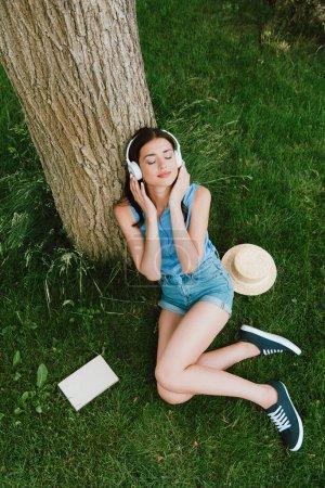 vista de ángulo alto de la hermosa mujer en ojos cerrados escuchando música mientras está sentado en la hierba cerca de libro y sombrero de paja