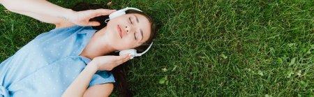 Photo pour Culture panoramique de belle femme couchée sur l'herbe et écouter de la musique - image libre de droit