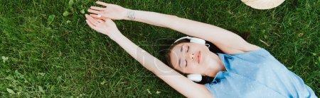 Photo pour Culture panoramique de femme attrayante couché sur l'herbe et écouter de la musique - image libre de droit
