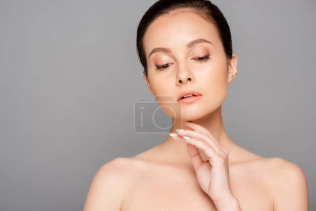 Photo for Beautiful naked woman with perfect skin touching face isolated on grey - Royalty Free Image