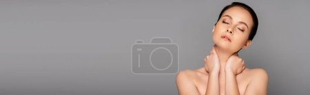 Photo for Beautiful naked woman with perfect skin and closed eyes touching neck isolated on grey, panoramic shot - Royalty Free Image